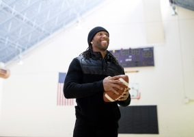 Larry Fitzgerald holding a football standing in a gym