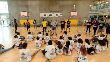 Seattle Storm staff standing in front of group of kids in a gym