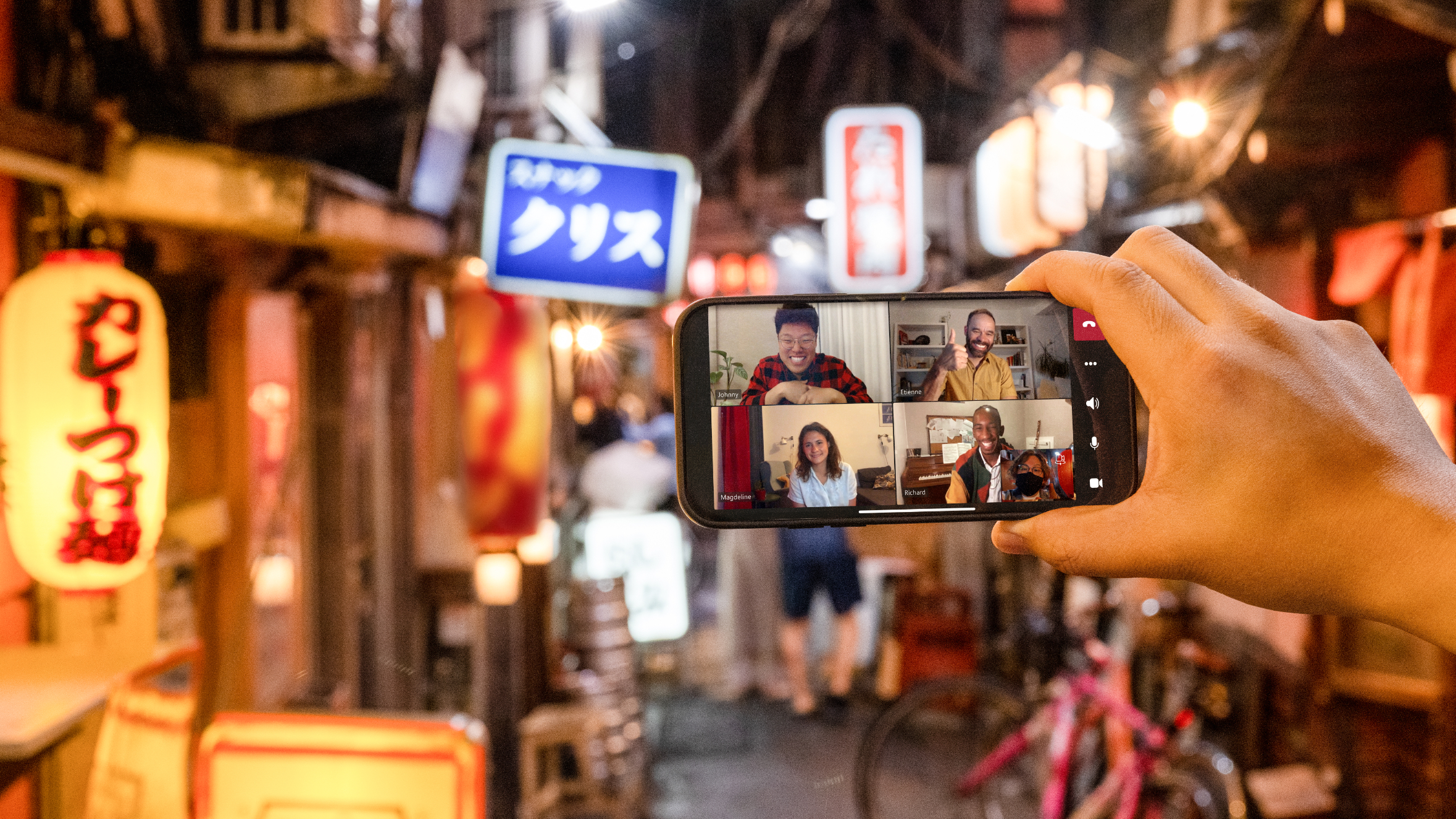 A Tokyo alley at night with a host sharing via Microsoft Teams.